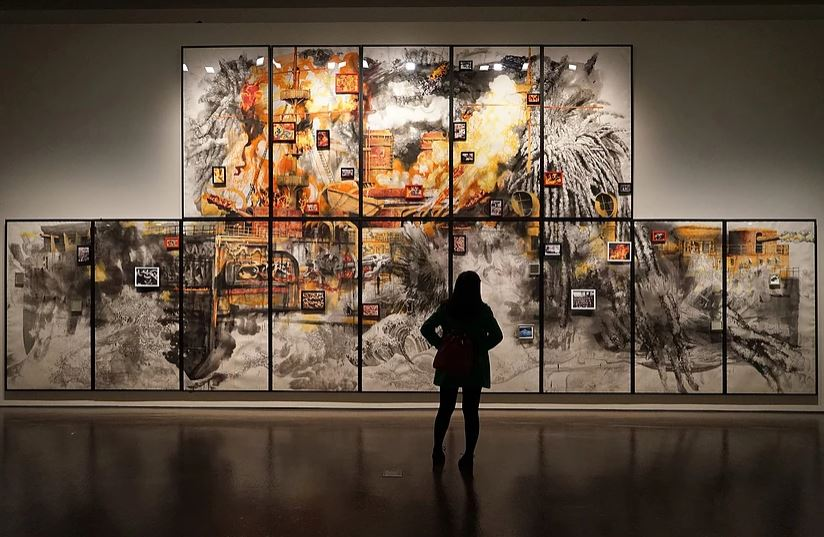 Solo female admiring very large artwork on the wall in a museum.