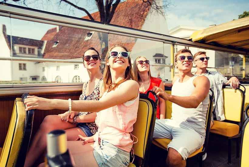 Travel with a tour group or go it alone. Happy tourists on a bus admiring the sites.