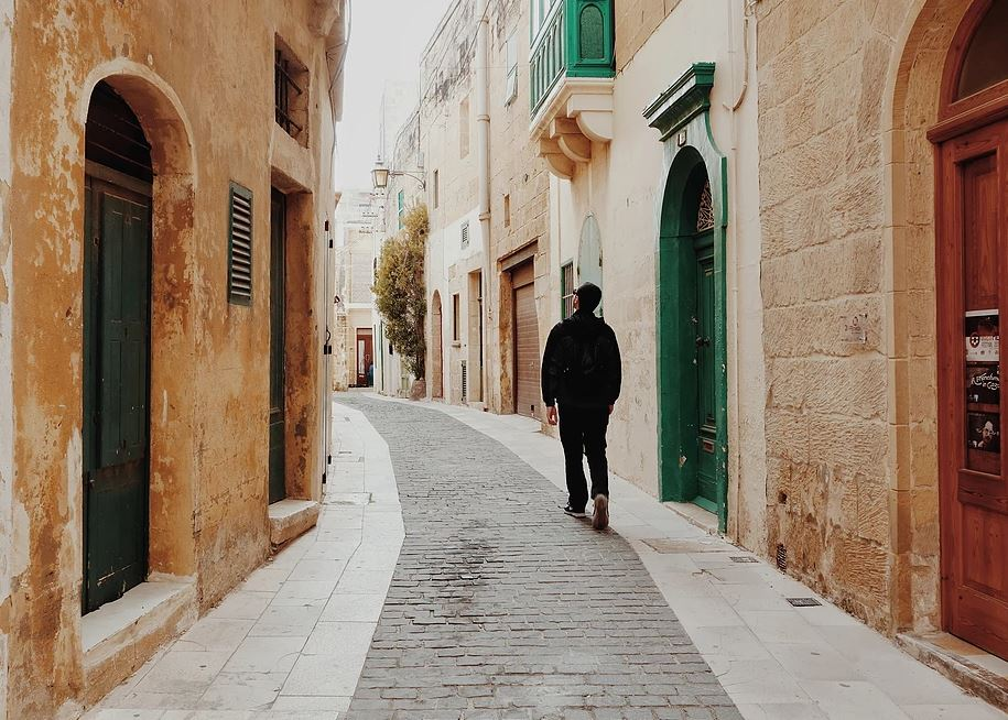 Man wandering alone on a cobblestone street